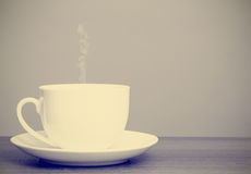White cup and saucer on wooden table with retro filter Royalty Free Stock Photos