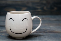White Cup with Smiley Face on Blue Wooden Table Royalty Free Stock Photography