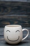 White Cup with Smiley Face on Blue Wooden Table Stock Photography