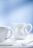 White cup and spoon with jug Royalty Free Stock Photo