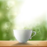 White cup standing on a wooden table in the garden Stock Image