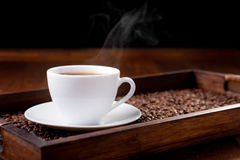 White cup of steaming coffee on a tray Stock Photos