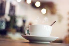 White cup with steaming hot coffee on table with bokeh backgroun Royalty Free Stock Photos