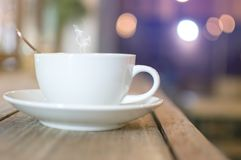 White cup with steaming hot coffee on wooden table Stock Photos