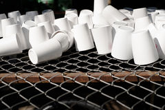 White cup on steel grating. White cup plastic on steel grating Royalty Free Stock Images