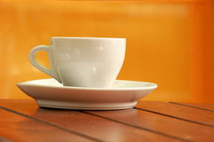 White cup on a table. White cup of coffee on a table Stock Images
