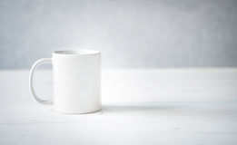 White cup on a table Stock Images