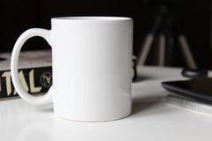 White cup on a table. White cup, mug on a table. Mockup for designs Stock Photos