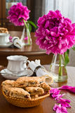 White cup of tea and biscuits and peony Stock Photo