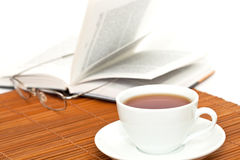 White cup of tea and book with glasses Royalty Free Stock Photos