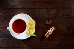 White cup of tea with cinnamon sticks, lemon, mint leaves and tea strainer on wooden rustic table. White porcelain cup of tea with cinnamon sticks, lemon, mint Royalty Free Stock Photo