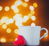 White cup of tea or coffee and heart shape toy with Fairy Lights royalty free stock images