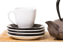 White cup of tea on different saucers with iron teapot on wooden Stock Photography