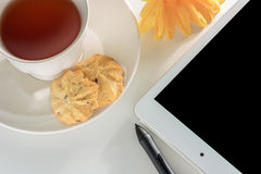 White cup of tea with digital tablet at simple workpl Royalty Free Stock Photo