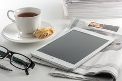 White cup of tea with digital tablet at simple workpl Stock Images