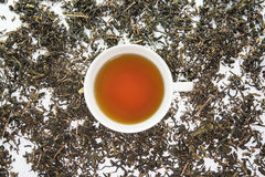A white cup of tea on the dry tea leaf Royalty Free Stock Photography