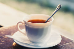 White cup of tea on a edge of wooden table Stock Photos