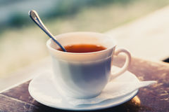 White cup of tea on a edge of wooden table Royalty Free Stock Image