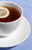 White cup of tea with lemon. On blue Stock Image