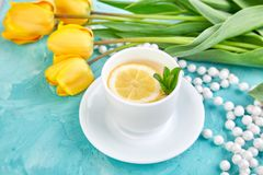 White cup of tea with lemon. Near yellow tulip on blue background. Flat lay. Mother or Woman Day. Greeting Card. Copy space. Spring. Summer. Beautiful stock images