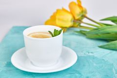 White cup of tea with lemon. Near yellow tulip on blue background. Flat lay. Mother or Woman Day. Greeting Card. Copy space. Spring. Summer. Beautiful royalty free stock image