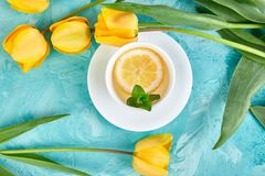 White cup of tea with lemon. Near yellow tulip on blue background. Flat lay. Mother or Woman Day. Greeting Card. Copy space. Spring. Summer. Beautiful royalty free stock photography