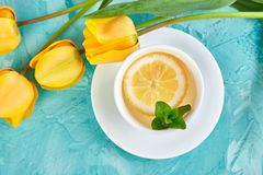 White cup of tea with lemon. Near yellow tulip on blue background. Flat lay. Mother or Woman Day. Greeting Card. Copy space. Spring. Summer. Beautiful stock photo