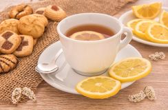 White cup of tea with lemon, pastries and cookies. Still life composition with a cup of tea over a wooden table with assorted pastries and cookies Royalty Free Stock Image