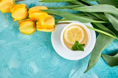 White cup of tea with lemon. Near yellow tulip on blue background. Flat lay. Mother or Woman Day. Greeting Card. Copy space. Spring. Summer. Beautiful stock image