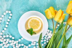 White cup of tea with lemon. Near yellow tulip on blue background. Flat lay. Mother or Woman Day. Greeting Card. Copy space. Spring. Summer. Beautiful royalty free stock photos