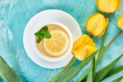 White cup of tea with lemon. Near yellow tulip on blue background. Flat lay. Mother or Woman Day. Greeting Card. Copy space. Spring. Summer. Beautiful royalty free stock photo