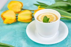White cup of tea with lemon. Near yellow tulip on blue background. Flat lay. Mother or Woman Day. Greeting Card. Copy space. Spring. Summer. Beautiful royalty free stock images