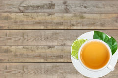 White cup with tea, lime and tea green leaves on wooden table ba Stock Photography