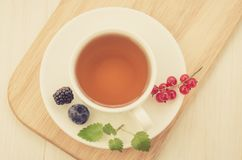 White cup tea with mint and berries in a saucer/white cup tea with mint and berries in a saucer on a wooden tray and a white. Background. Top view. Toned stock image