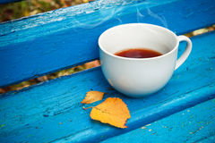 White cup of tea is on old blue wooden bench Stock Photo