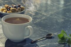 White cup with tea, pancakes with currant jam. Vanilla tone stock images