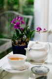 A white cup of tea with purple flower. On classic table Royalty Free Stock Photo