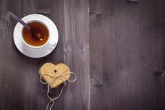 The White cup of tea and saucer on a brown wooden table. Copy space. White cup of tea and saucer on a brown wooden table. Copy space Stock Photography