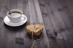 The White cup of tea and saucer on a brown wooden table. Copy space. White cup of tea and saucer on a brown wooden table. Copy space Royalty Free Stock Photography