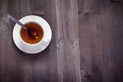 The White cup of tea and saucer on a brown wooden table. Copy space. White cup of tea and saucer on a brown wooden table. Copy space Royalty Free Stock Images