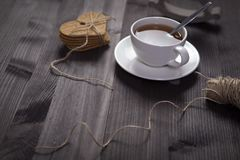 The White cup of tea and saucer on a brown wooden table. Copy space. White cup of tea and saucer on a brown wooden table. Copy space Stock Image