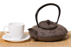 White cup of tea on saucer and iron teapot on wooden mat. Royalty Free Stock Photos