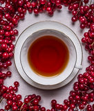 White cup of tea on a saucer on a white wooden background frame of red berries Viburnum  close up top view Stock Image