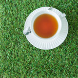 A white cup of tea with silver spoon on the green grasses Royalty Free Stock Photos