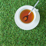 White cup of tea with spoon on the grasses from top view Royalty Free Stock Images