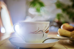 White cup of tea. Steam rises over the white teacup with hot tea on the table in the room Royalty Free Stock Images