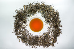 White cup of tea surrounded by dried tea leaf Royalty Free Stock Images