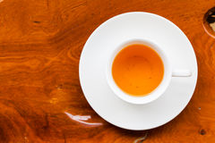 White cup of tea on wood table. White cup of fresh tea on wood table, view from above stock image