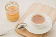 White Cup of tea on a wooden tray and jar of honey/white Cup of tea on a wooden tray and jar of honey. Selective focus. Open table background hot drink morning stock photo