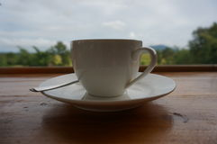 A white cup with teaspoon. On wooden table, natural background Royalty Free Stock Images
